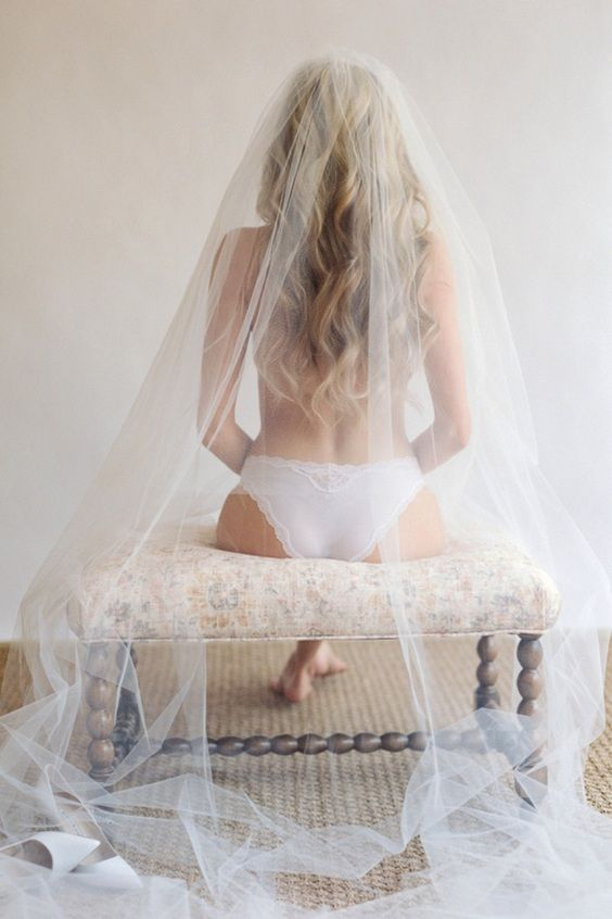 Nude bride getting dressed for wedding